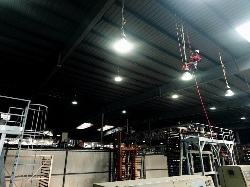 Prace instalacyjne, pracownik na wysokości na hali magazynowej, Climbnet