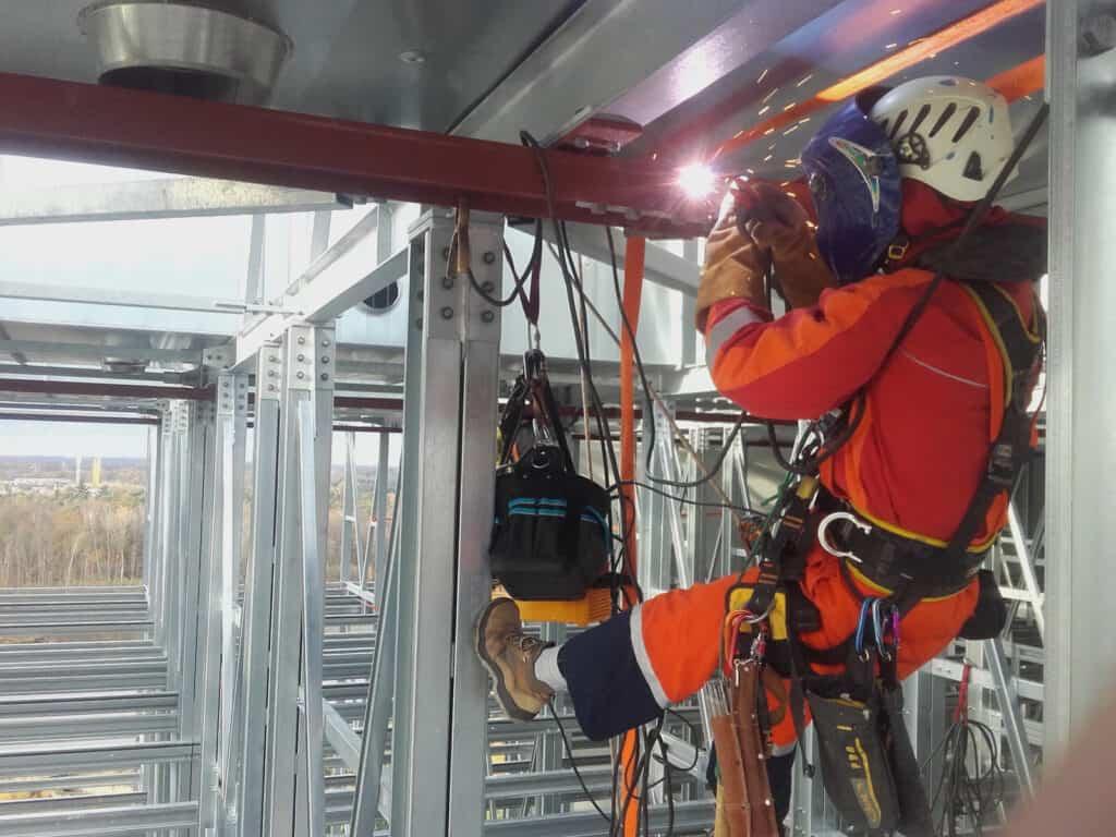 Spawanie na wysokości, instalacja metalowa, maska i rękawice spawalnicze, Climbnet