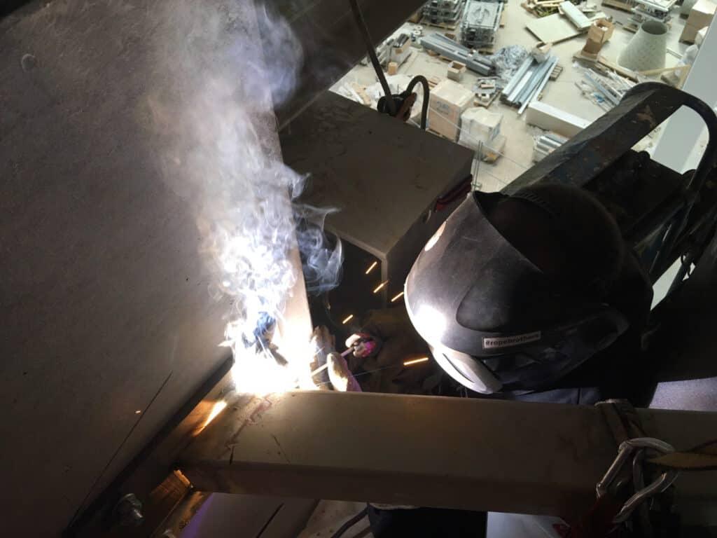Spawanie wewnątrz hali magazynowej, maska spawalnicza, dym