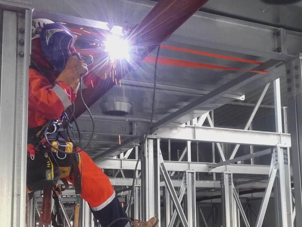Wykonywanie spawania w hali, przy instalacji metalowej, maska i rękawice spawalnicze, Climbnet