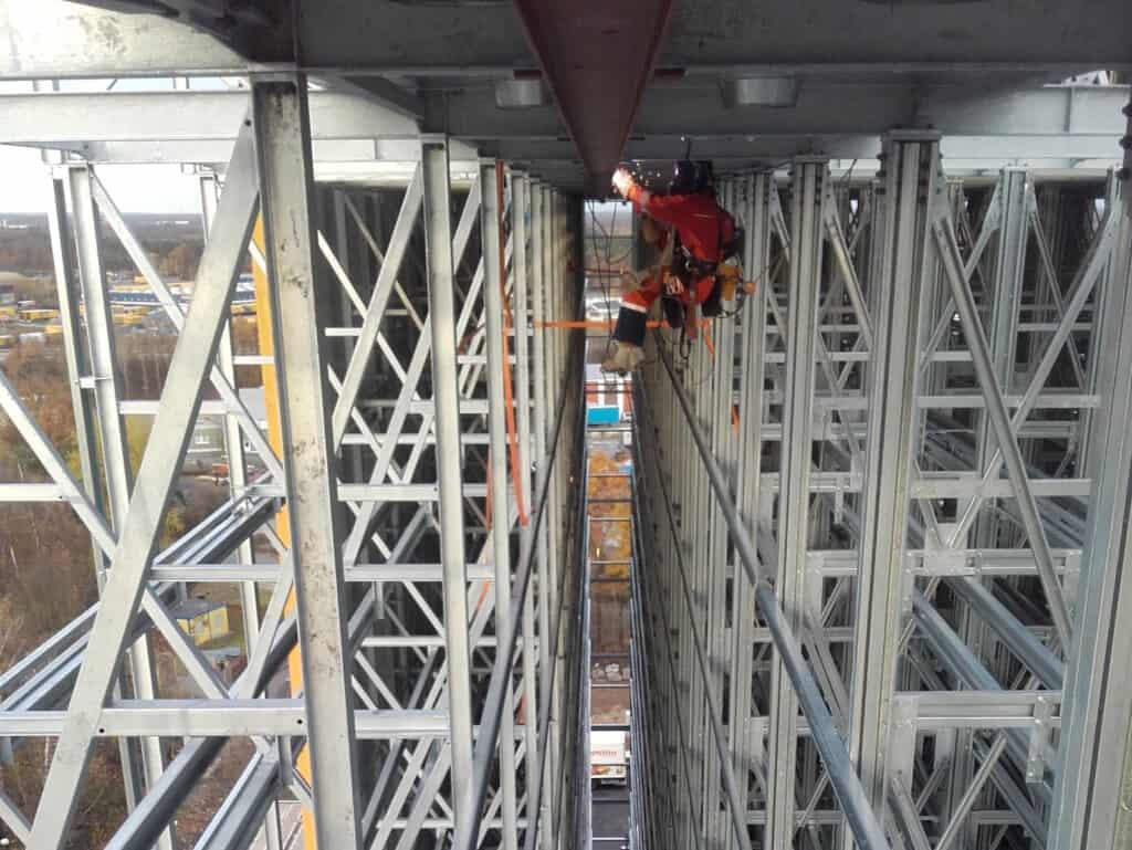 Montaż instalacji przemysłowych, spawanie na wysokościach, pracownik na wysokości w masce spawalniczej, Climbnet